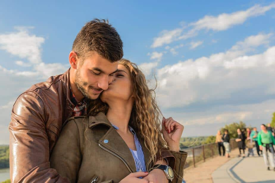 Couple cuddling against sky and river backdrop